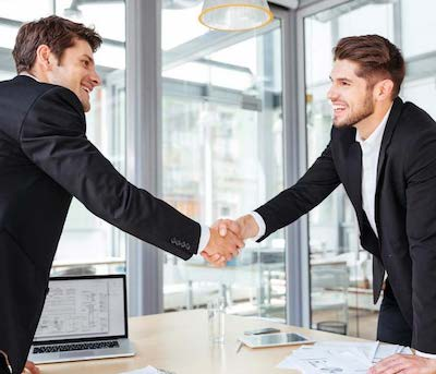 two men shaking hands across a meeting room table